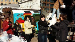 Frivilliga lastar av påsar med mat som ska delas ut till flyktingar i Kiev.