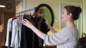 Rinna Saramäki ripustaa vaatteita rekkiin.