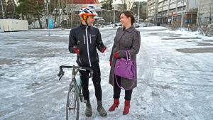 Fritjof Sahlström och Charlotte Vainio står vid hans cykel på parkeringsplatsen.