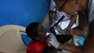 Camilla Storm granskar tänderna på ett av sina fadderbarn