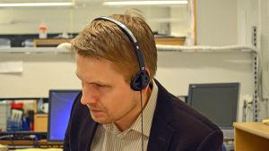 Aarne Kiviniemi lyssnar på en intervju med en arg butiksägare i Tölö.