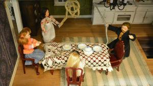 Gräl över hushållssysslor i ett dockhus.