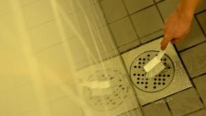Tvätt av golvbrunn med diskborste.