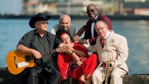 Fem musiker ur Buena Vista Social Club sitter vid kajkanten. Bland dem Eliades Ochoa och Omara Portuondo.