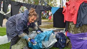 Konstnären Kaarina Kaikkonen rotar efter nästa plagg att hänga upp.