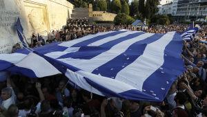 Demonstranter som vill att Grekland stannar kvar i EU håller upp den grekiska flaggan utanför parlamentet i Aten.