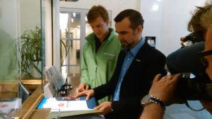 Greenpeace informatör Juha Aromaa överlämnar protestlista mot Fennovoima till Arbets- och näringsministeriet.