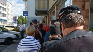 Människor väntar på mat i en lång brödkö i Åbo.