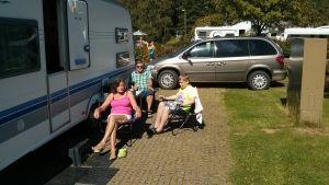Lilja tekoniemi med familj sitter utanför sin husvagn på Rastböle campingområde