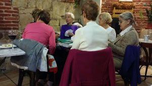 Kuusi vanhahkoa naista pelaa korttia baarissa Espanjassa