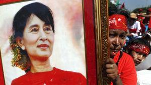 En anhängare av aung san suu kyui bär hennes bild inför valet i Burma  i november 2015.