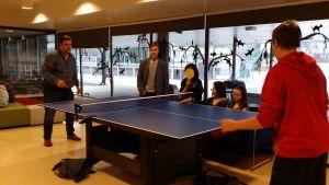 Pingispöytä ja pelaajia koulun aulassa