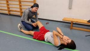 Liikunnanopettaja hieroo oppilaan jalkoja