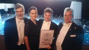 Neljä juhla-asuista henkilöä hymyilevät, kuvassa myös palkintodiplomi.