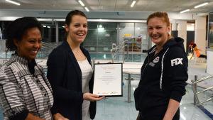 Muluken cederborg och Elin Andersson delar ut diplom åt simhallschef Laura Kuutti i Malm.