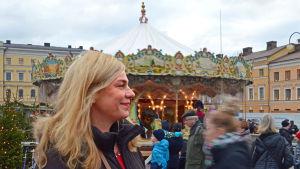Peggy Bauer, chef för Torgkvarteren, poserar framför karusellen hon beställt till Tomasmarknaden.
