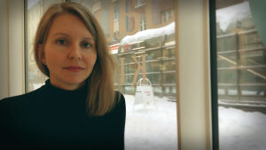 Nora Hämäläinen tittar in i kameran, genom fönstret bakom ser man en snöig gatubild.