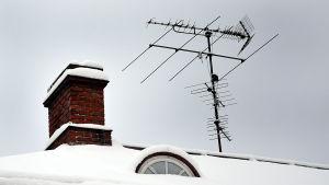 Tv-antenner på tak med gammal skorsten.
