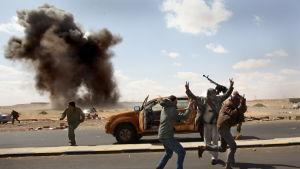 Milismän utanför Ras Lanuf söker skydd då en granat exploderar nära dem