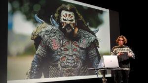 Antti Haase kertoo Monsterimies-elokuvastaan, taustalla Lordin kuva