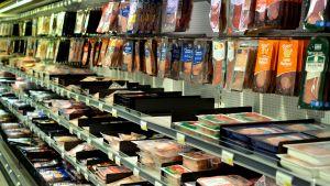 Hylla med köttprodukter i mataffär.
