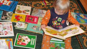 Lapsi katselee kirjaa.