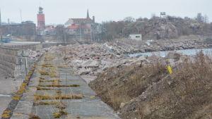 Stenbumlingar väntar på stranden för att bli vågbrytare i Västra hamnen i Hangö.