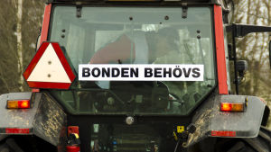 """Traktor med banderoll där det står """"Bonden behövs""""."""