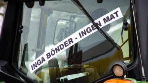 """Traktor med banderoll där det står """"Inga bönder - ingen mat""""."""