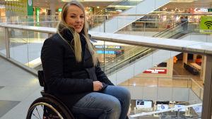 Anni Täckman sitter i en rullstol i ett köpcentrum