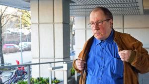 Ledande socialarbetare Bengt Lindblom utomhus, tar på sig rocken.