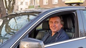 Taxichauffören Kaj Rönnholm tittar ut genom fönstret i sin taxi