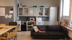 En klassrum med en soffa, ett bord och en liten kaffe-hörna.