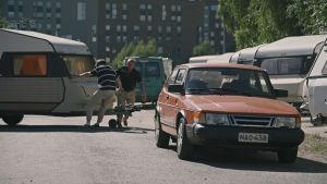Kasper Strömman och Pehr-Olof Eklund kopplar en husvagn bakom en röd Saab.