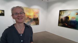 Margareta von Bonsdorff framför två av sina målningar på Galleri Bronda 2016.