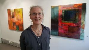 Margareta von Bonsdorff mellan sina målningar Purkautumaton jännite och Allting förändras på Galleri Bronda 2016.