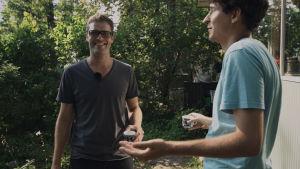 Kasper och Jussi dricker kaffe i trädgården