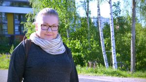 En kvinna med glasögon i halvbild.