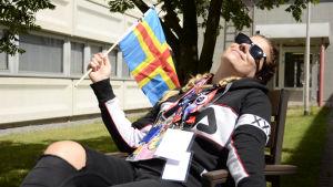 Pernilla Karlsson solar med Ålands flagga i handen