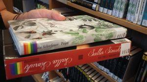 """Jessica Schiefauers ungdomsbok """"Pojkarna"""" och Salla Simukkas ungdomsbok """"Kun enkelit katsovat muualle"""" med regnbågsklistermärken på ryggen."""