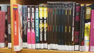 En rad böcker på en bokhylla. En har ett regnbågsklistermärke på ryggen.