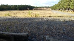 En skjutbana på sandig mark. I förgrunden två stockar, i bakgruden syns en vall, på sidorna skog. Sol och skugga.