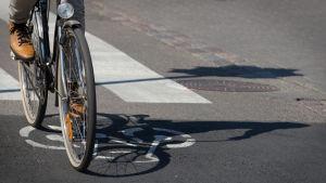 Anonyymi mies polkee pyörää pyöräkaistalla kaupungissa kesällä.