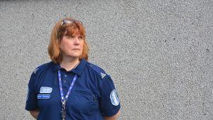 Poliskommisarie Heidi Warelius står framför grå vägg, blickar allvarligt i fjärran.