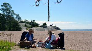 Ett par har picknick på en strand. I bakgrunden syns en midsommarstång.