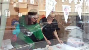 Jolin Slotte och Pauliina Pesonen genom skyltfönstret till Galleri Kalleria.