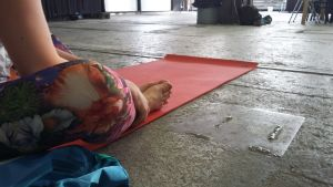 En person sitter på en yogamatta med mönstrade yogabyxor.