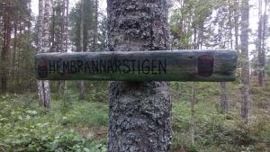 träskylt uppspikad på träd