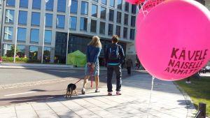 Två kvinnor med en hund och en bellong i förgrunden.