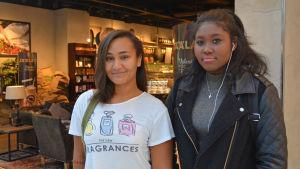 Två tonårsflickor står utanför café i köpcentrum.